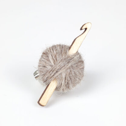 grey ball of wool with crochet hook on a white background
