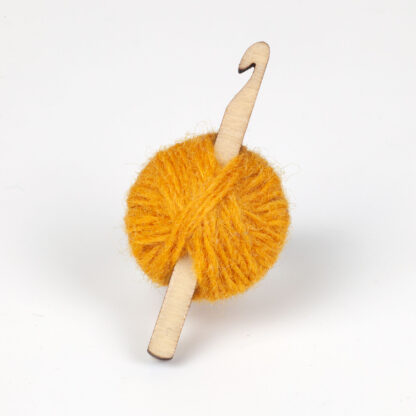 yellow ball of wool with crochet hook on a white background