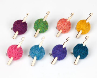 8 balls of wool with crochet hooks in