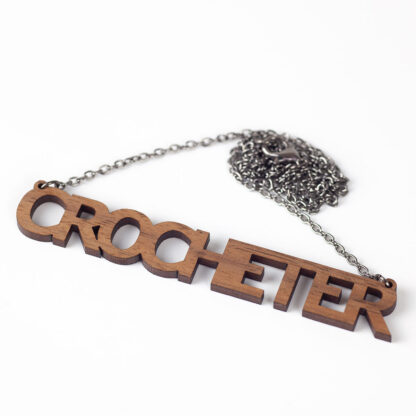The word crocheter laser cut from walnut veneer wooden a dark chain