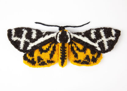 A knitted black, white & yellow moth on a white background
