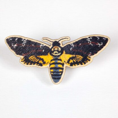 wooden pin with a knitted deaths head hawkmoth printed on it.
