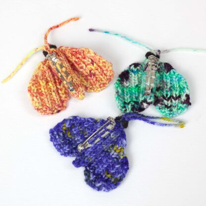 underside of 3 knitted moths with brooch bars sewn on