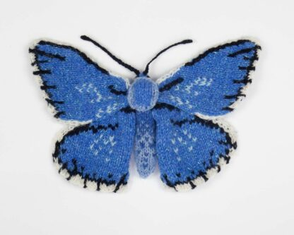 Knitted blue butterfly with black and white details