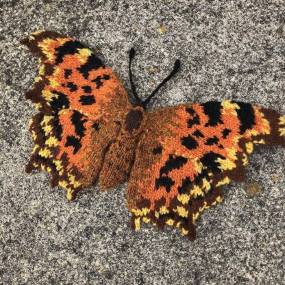 knitted orange and brown butterfly on concrete