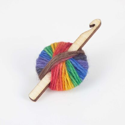 A brooch made with rainbow yarn and a wood crochet hook