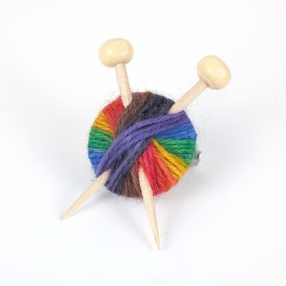 A brooch made with rainbow yarn and 2 wooden knitting needles