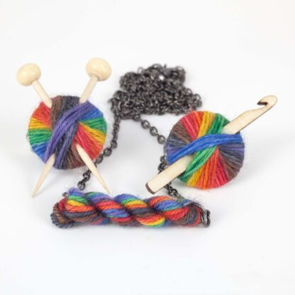 necklace and 2 brooches with pride rainbow yarn