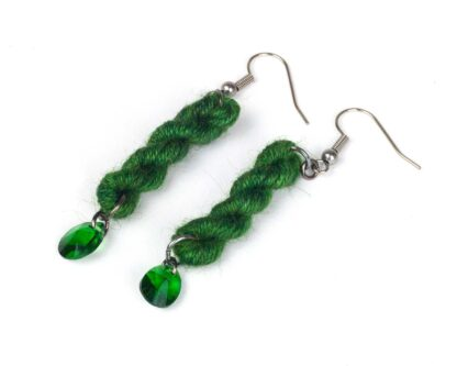 green earrings made with a tiny skein of yarn and green crystal hanging from the bottom