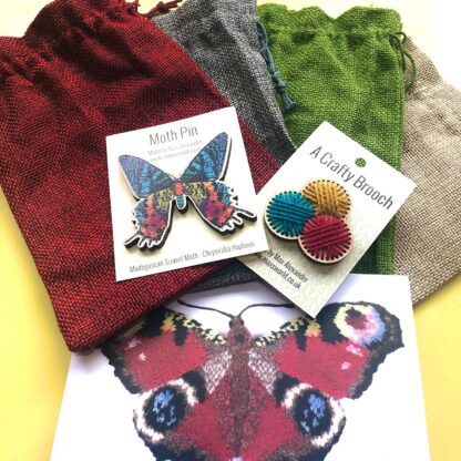 4 colourful hessian bags with 2 wooden brooches on top and a greeting card below.