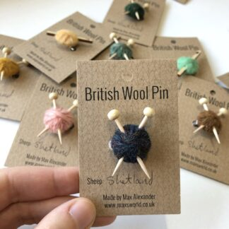 Pins made from balls of wool with either knitting needles or a crochet hook in.