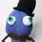 knitted head with moustache and top hat